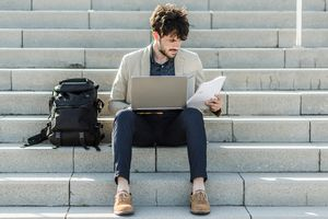 College student organizing his schedule with a notepad and paper witting next to a backpack