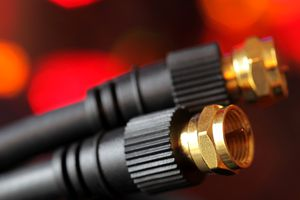 Two coaxial cables in front of a red background.