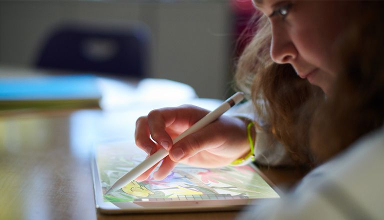 A young girl using an iPad with they Apple stylus, to draw a picture.