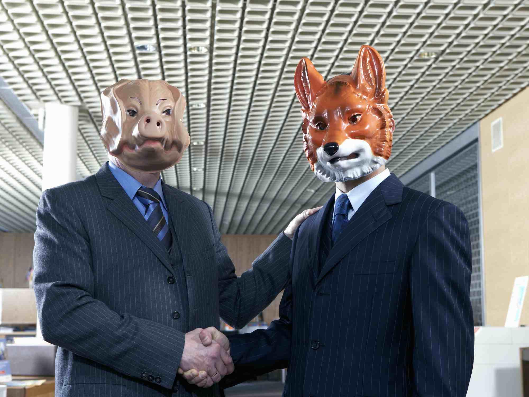 Businessmen shaking hands with animal masks