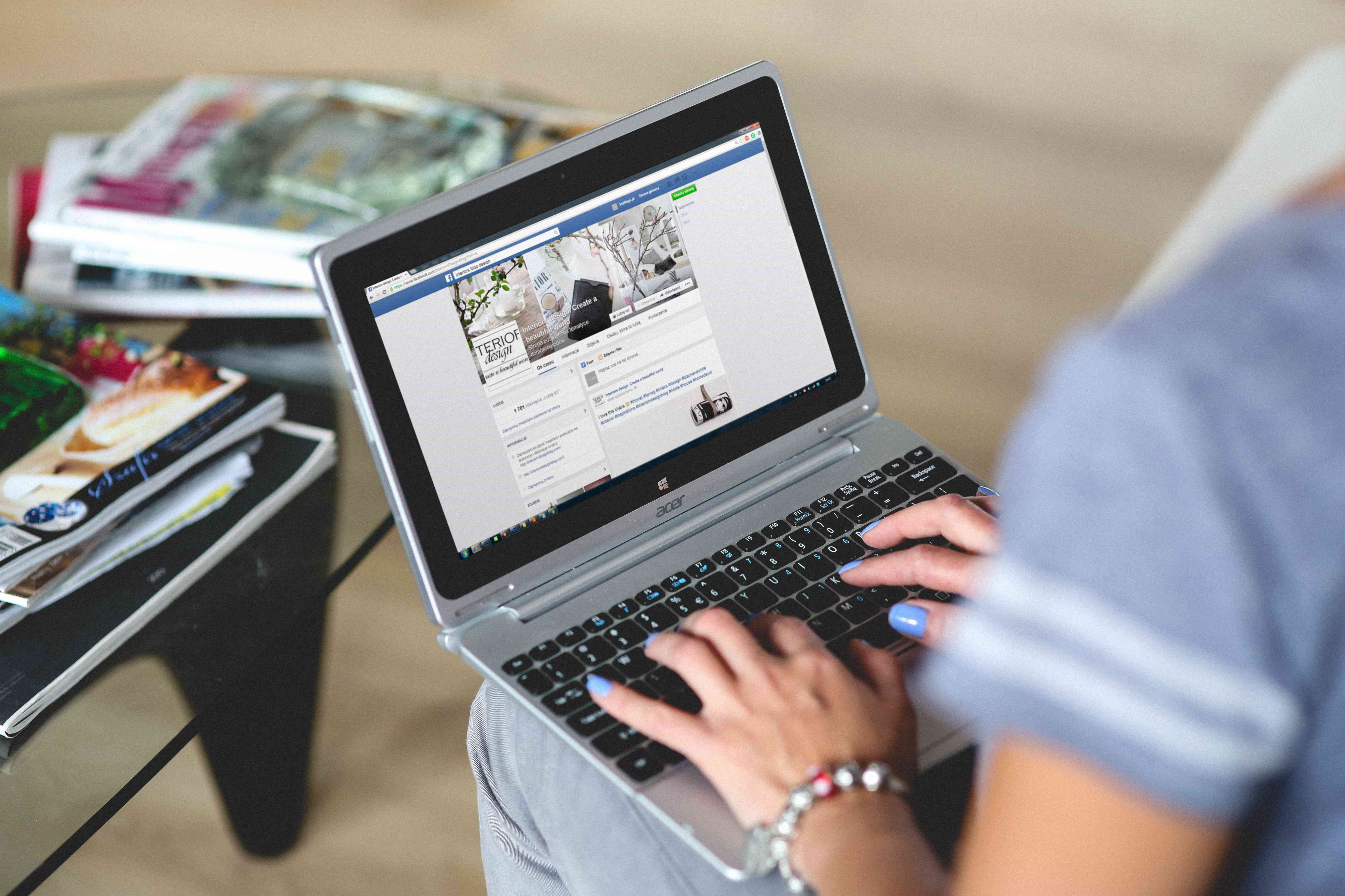 An image of a woman looking at a Facebook page on a laptop.