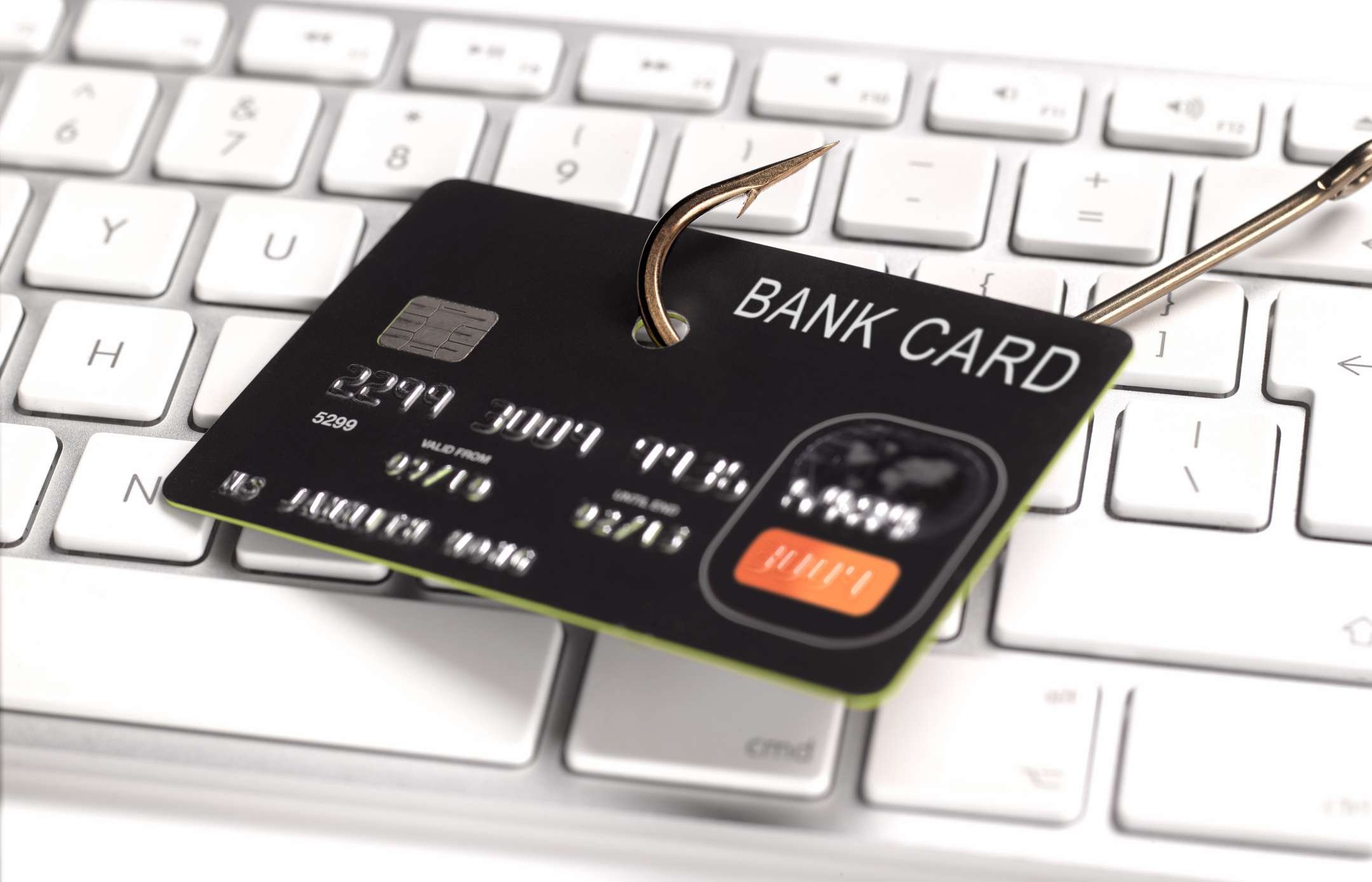 A security concept image of a credit card with a fish hook through it laying on a computer keyboard.