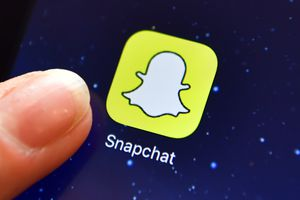 A finger is posed next to the Snapchat app logo on an iPad