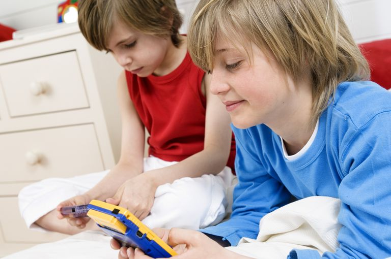 Two boys playing GameBoy games.
