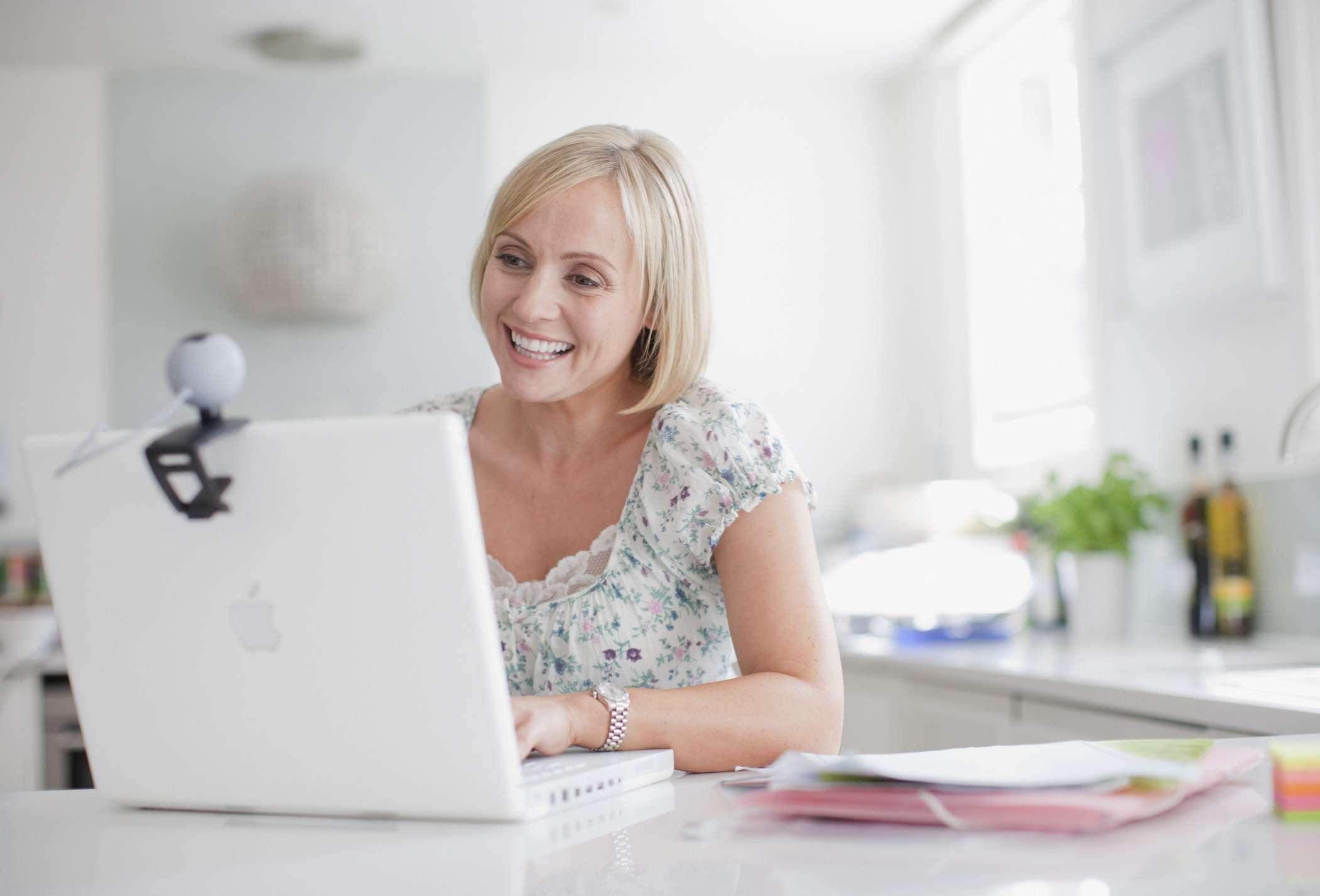A woman using a webcam on a laptop computer.