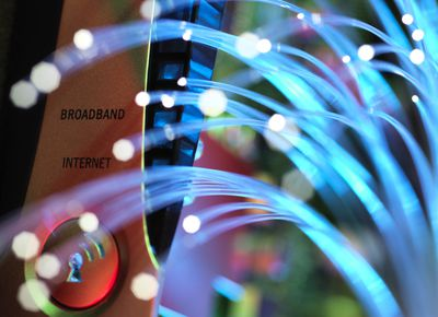Fiber optic cables glowing in front of a router