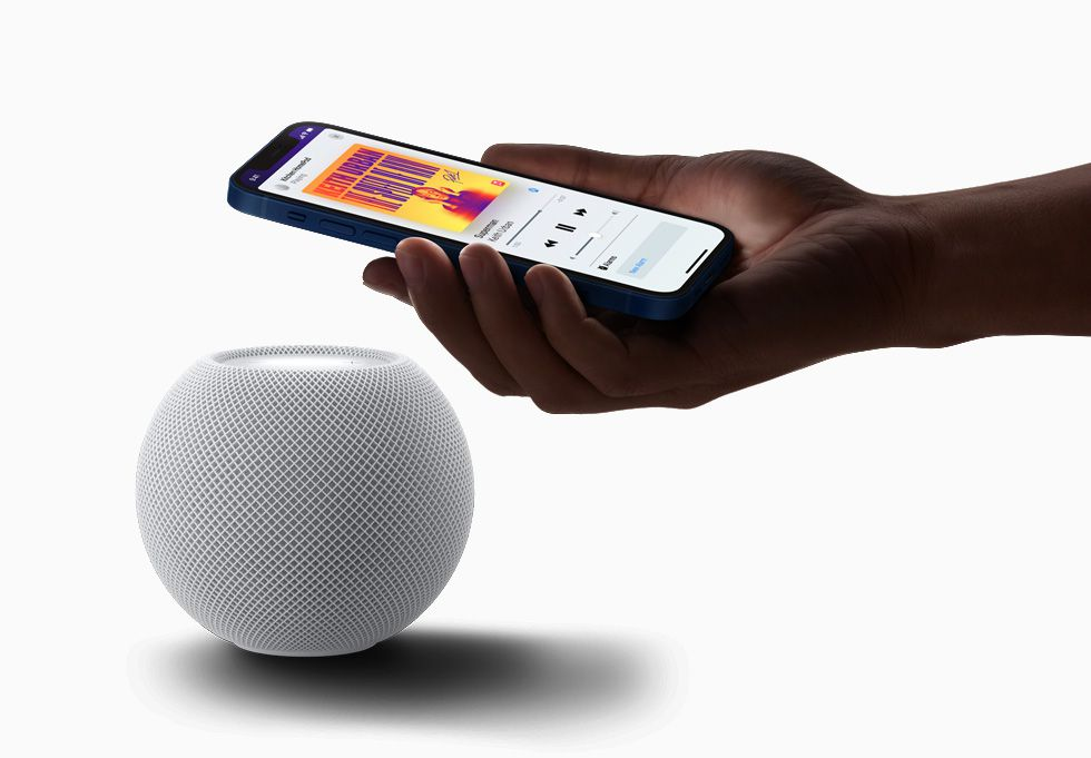 iPhone held next to white HomePod Mini
