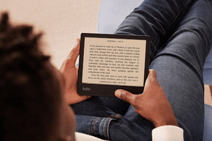 Someone lounging in a chair reading on a Kobo e-reader.