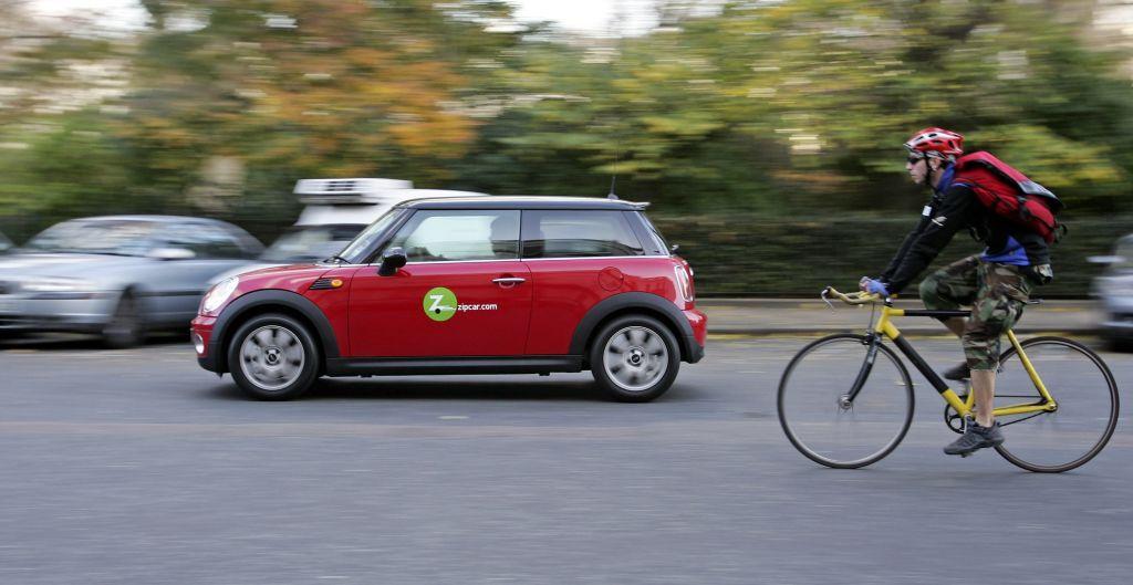 A Zipcar drives past a cyclist,