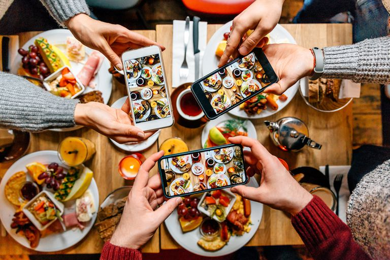Multiple people taking photos of a meal spread on a table