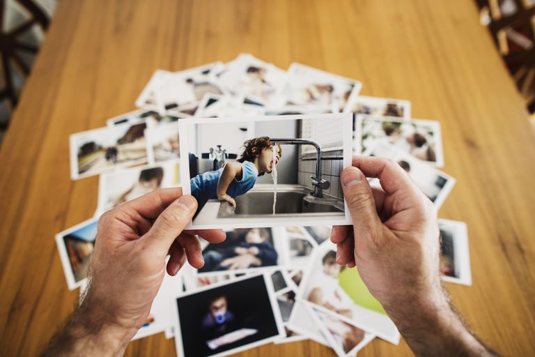 Close up of polaroid held in hands with stack of photos behind