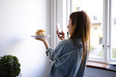 Woman taking a photo with her iPhone of a plate of waffles