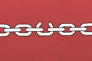broken chain link on red background