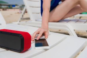 Female hand with phone and bluetooth speaker at beach