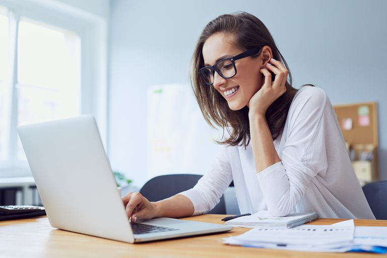 Young businesswoman working on laptop and laughing in home office.