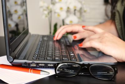 Woman using laptop with glasses on desk