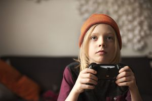 A child holding a games controller staring intently at a screen off-camera