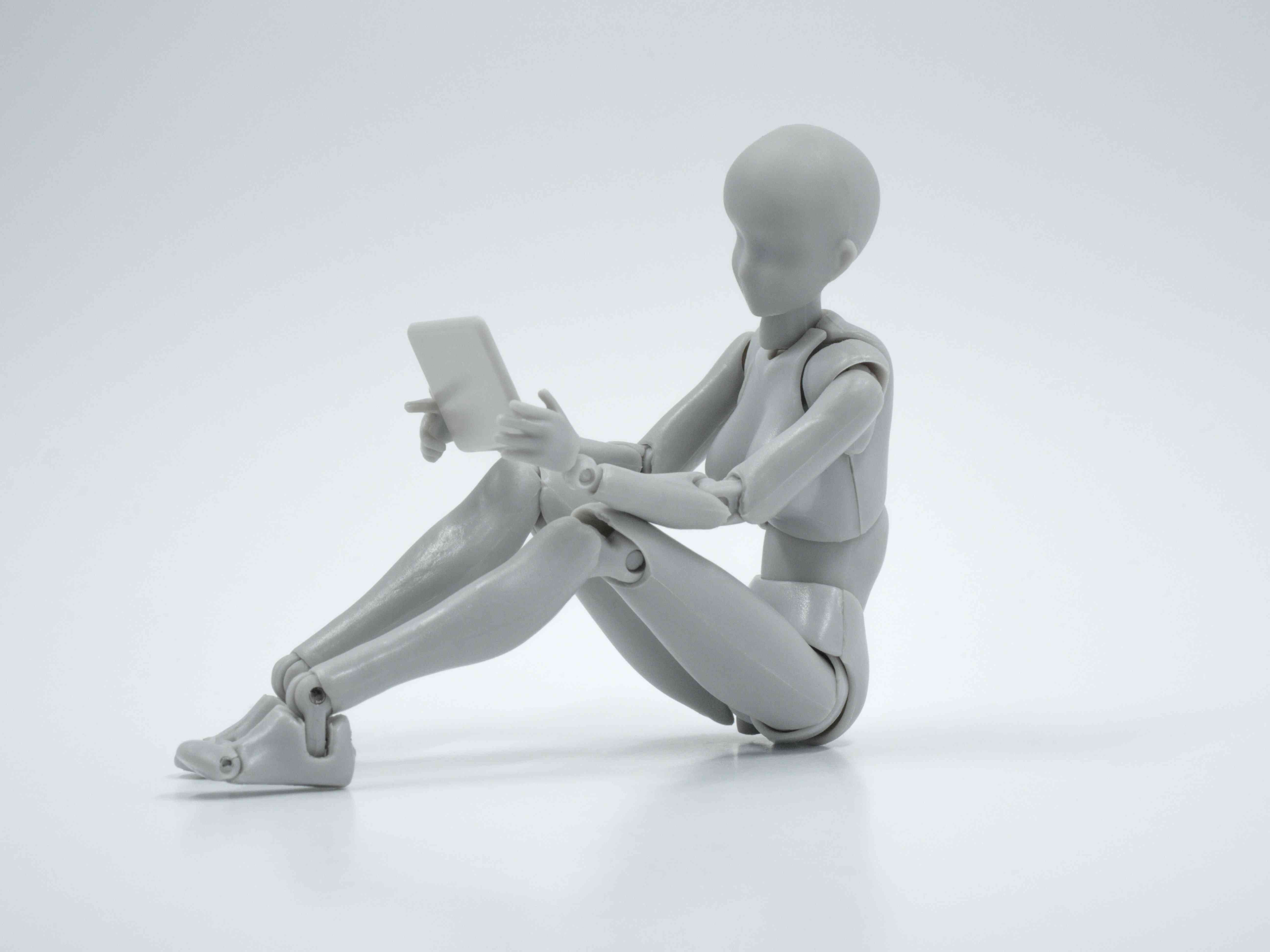 A plastic figuring with only minimal features, holding a tablet as if reading from it.