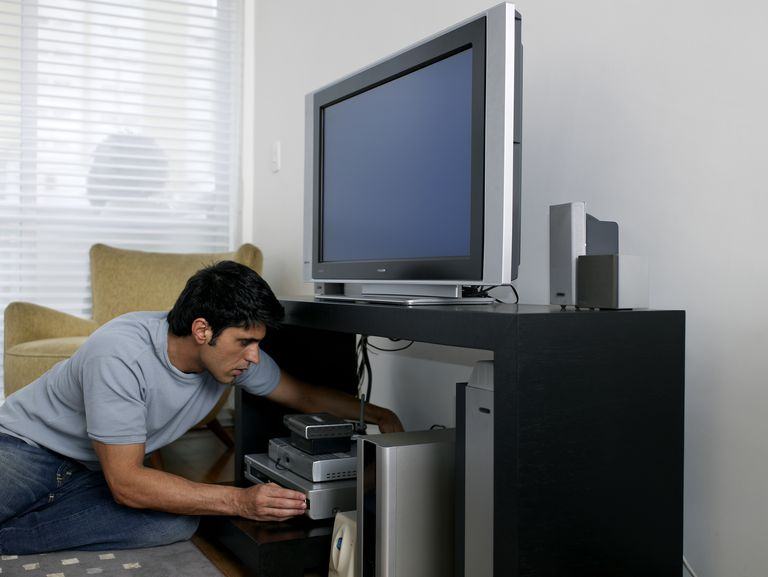 Mid adult man fixing television cable, side view