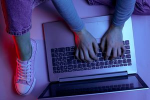 A woman wearing purple jeans, t-shirt, and shoes typing on her laptop.