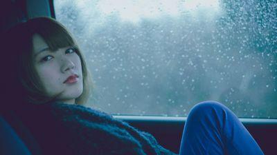 A woman sits in a cold car that's in need of a replacement aftermarket car heater.