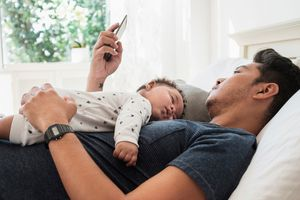 Father lying with his baby on his chest in bed while checking a sleep app on his iPhone