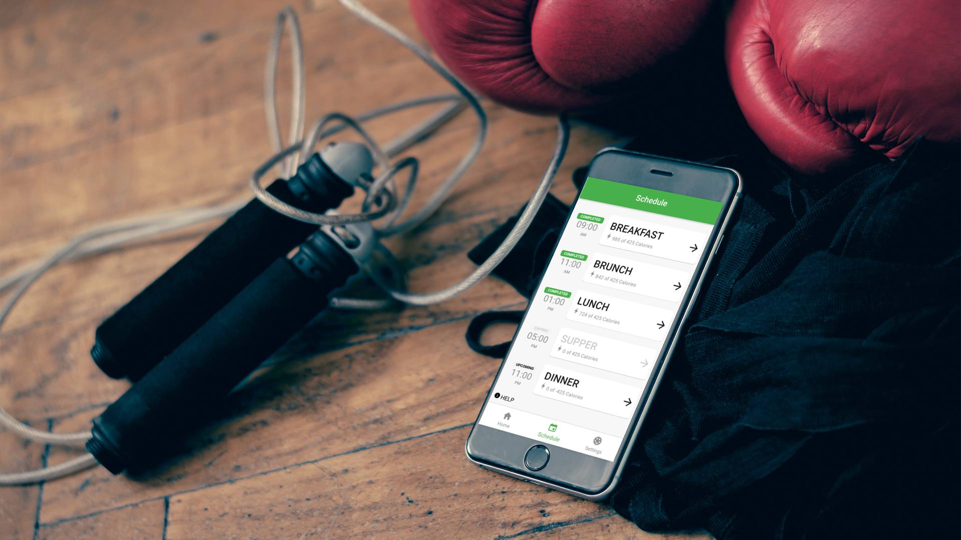 GainGuy app running on iPhone next to skipping rope and boxing gloves