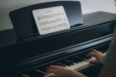 Musician playing piano with notation on tablet pc