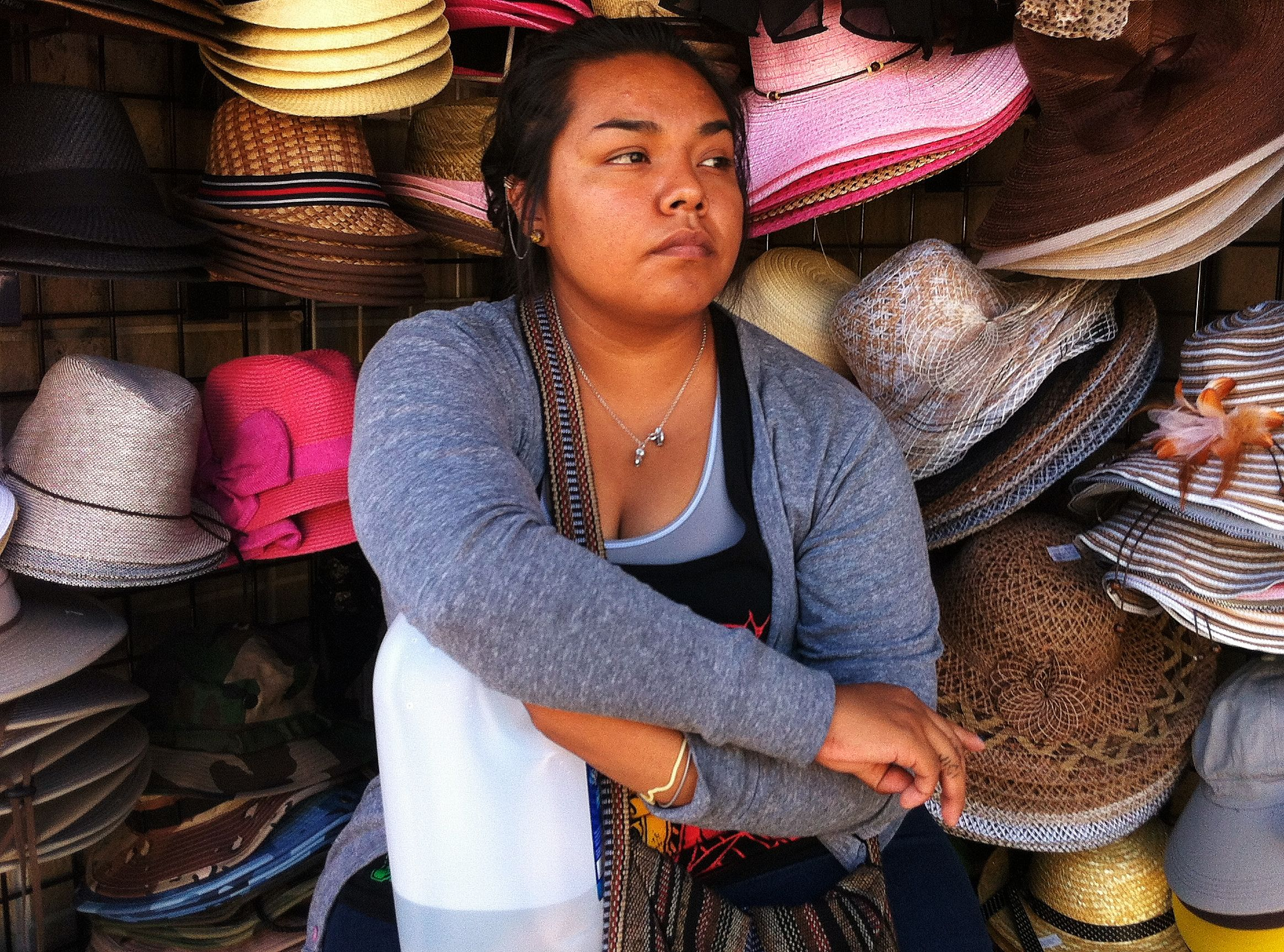 Woman sitting in front of hat display