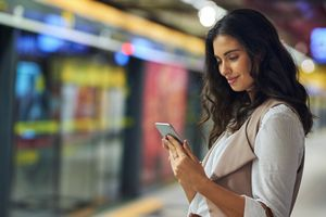Young woman with smartphone on train platform