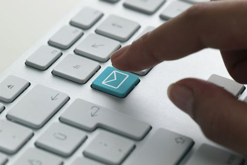A finger pressing an email key on a keyboard