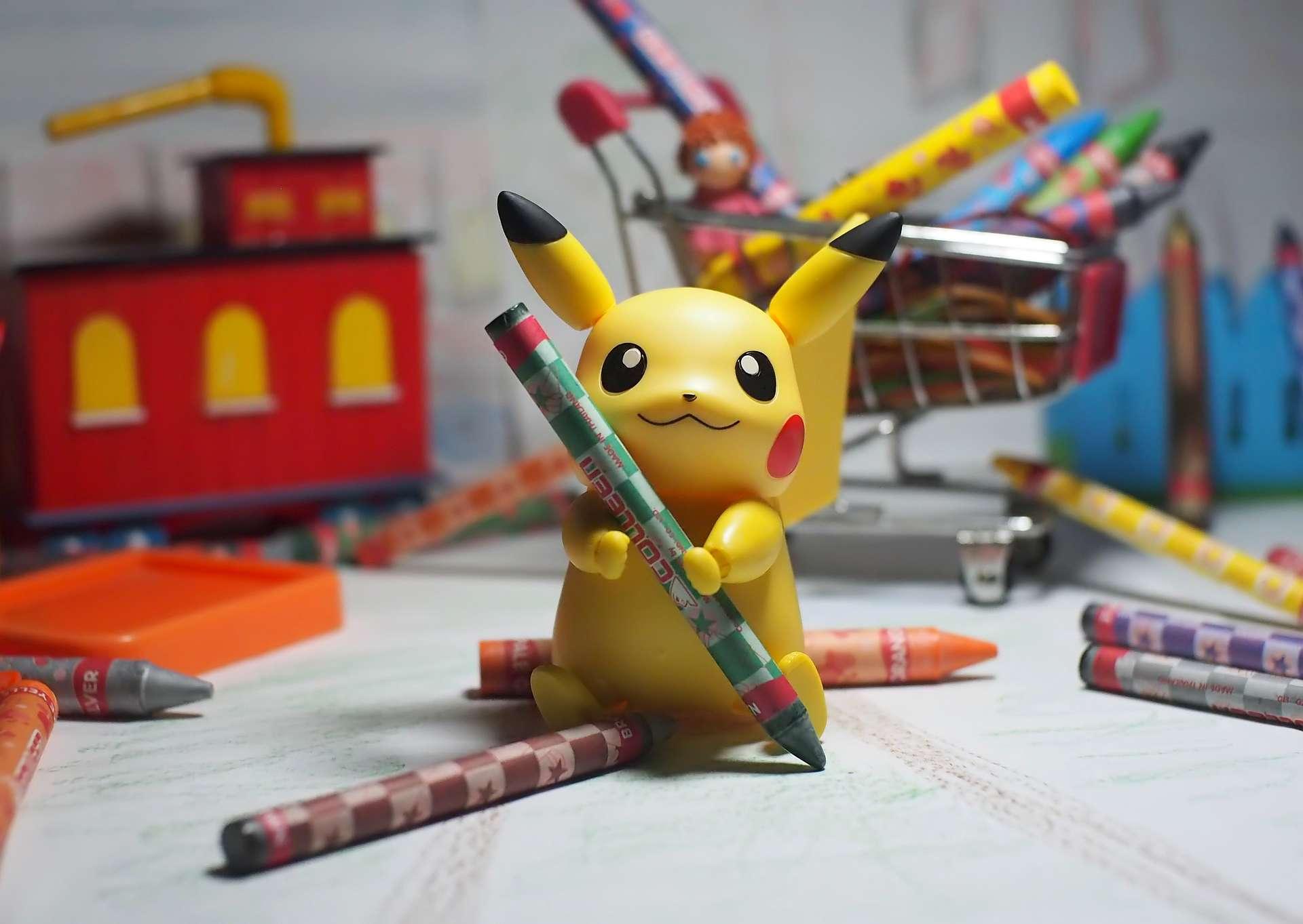 Pikachu Pokemon character holding crayons.