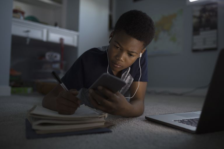 An image of a child looking at his smartphone while studying.
