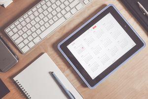 A photo of an iPad with the calendar app open on a desk