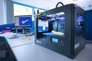 3D printing machine with CAD design on screen in orthopaedic factory