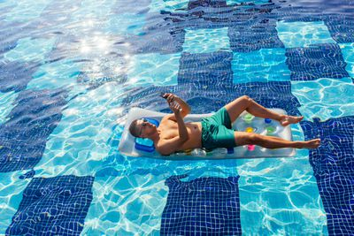 A man lying on an inflatable in a swimming pool looking at his smartphone