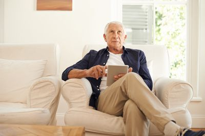 Man sits on chair while using his tablet and looking towards the ceiling.
