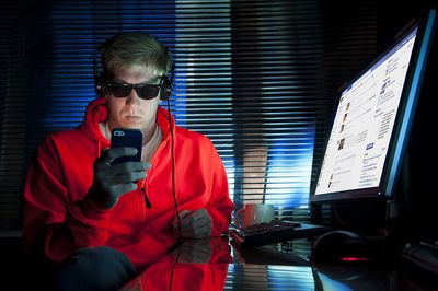 Someone sitting in front of a a brightly lit computer at night, looking at a smartphone, while wearing sunglasses.