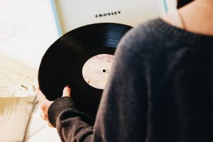 Over the shoulder view of someone holding a vinyl record.