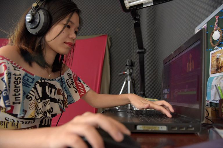 A young woman working on videos at her computer.