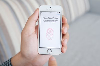 Hand holding iPhone with Touch ID on the iPhone screen