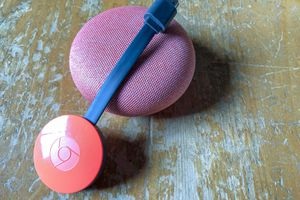 A red Chromecast propped against a pink, cloth-covered Google Home Mini.