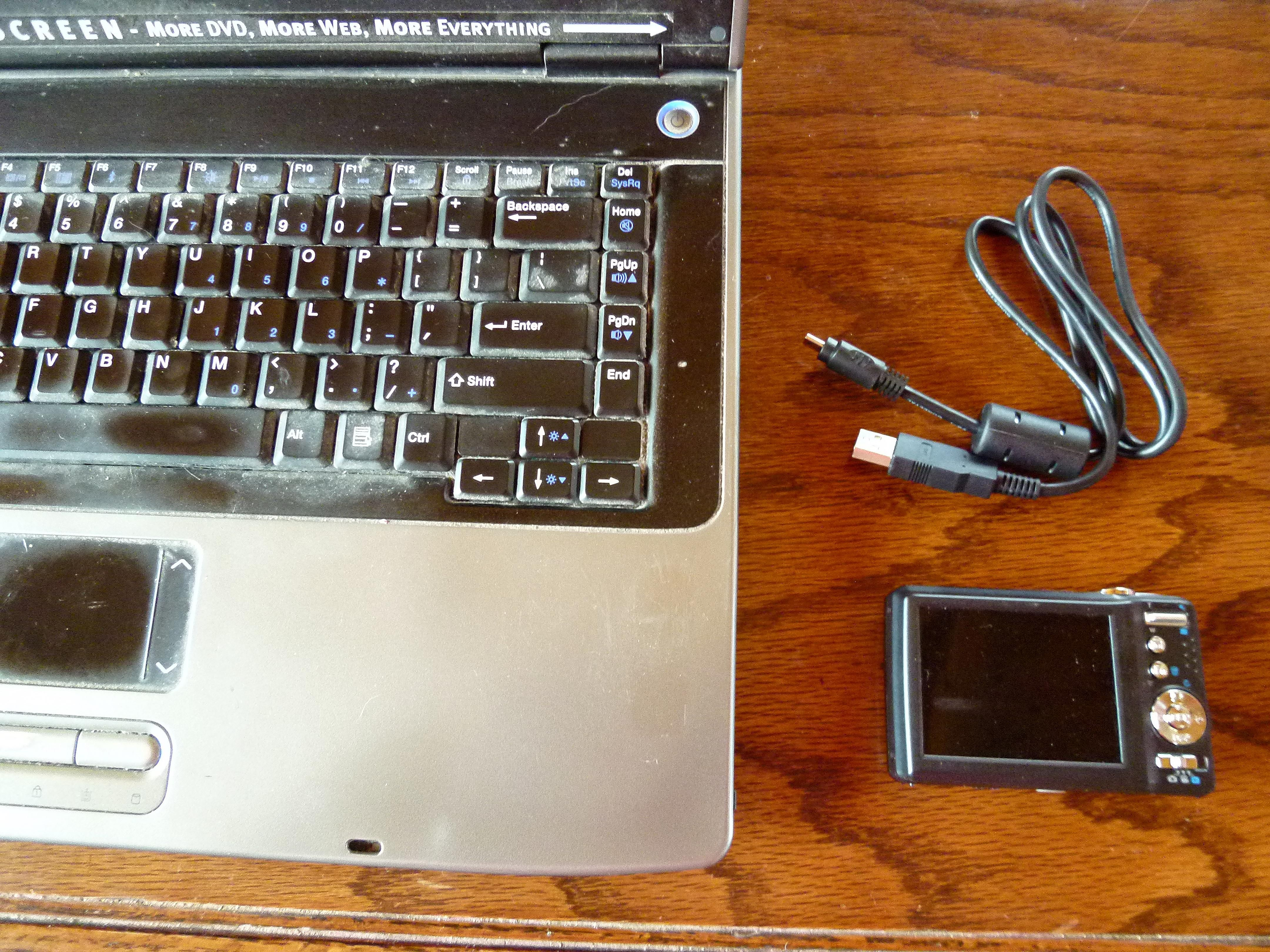 laptop with digital camera and cord next to it