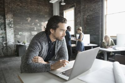 Business owner working at laptop in open plan office