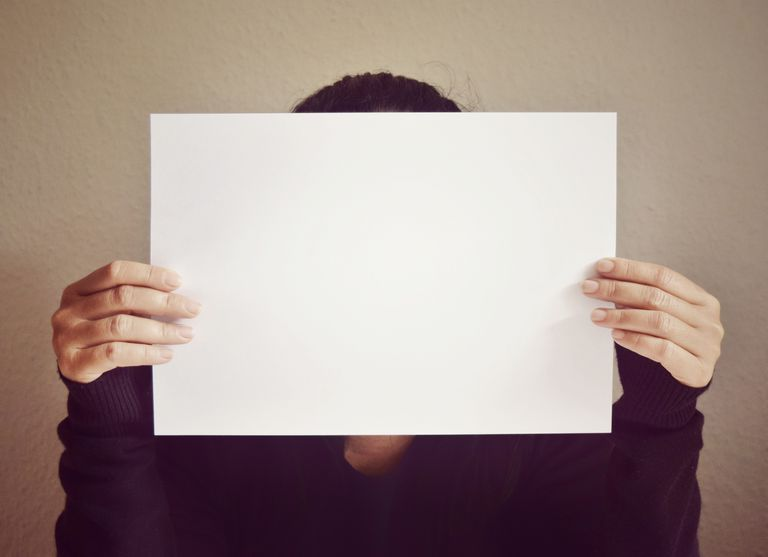 A woman holding up a blank sheet of paper.