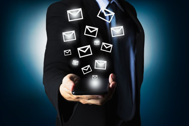 man with email icons floating above his cell phone