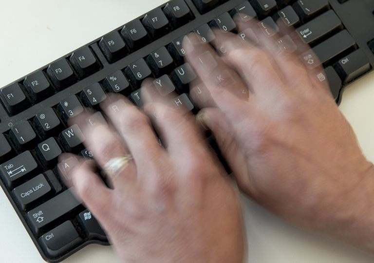 A man typing quickly on a keyboard