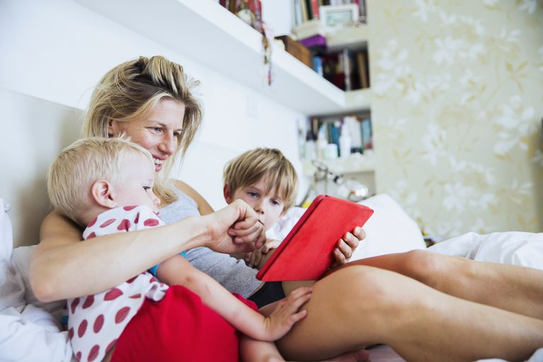 A mother plays with an iPad with her kids.
