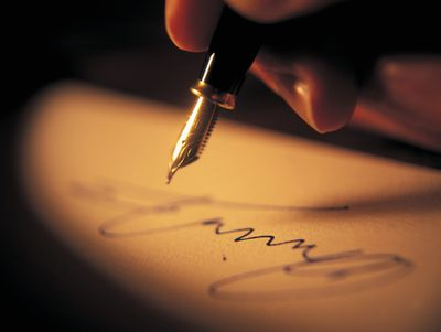 Fountain pen hovering over a recently completed signature on paper