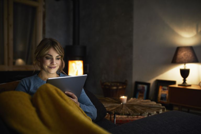 Portrait of smiling woman with tablet relaxing on couch in the evening